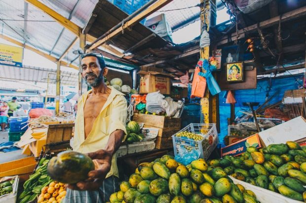 A colourful fruit market has a man outside holding a mango
