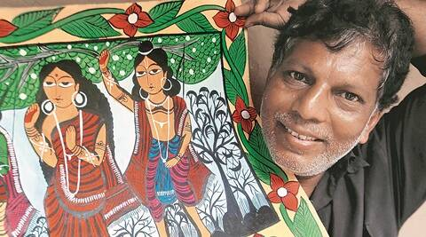 Yakub Chitrakar shows a scroll painting depicting incidents from Ramayana at his home at Noya in West Midnapore. (Source: Express photo by Subham Dutta)
