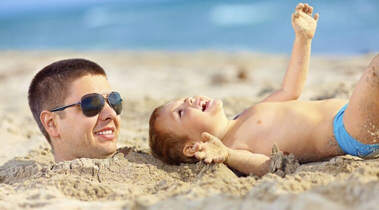 father and son having fun in sand, laughing on beach