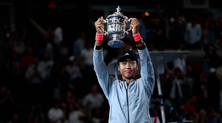 Naomi Osaka, of Japan, holds up the championship trophy after defeating Serena Williams in the women's final of the U.S. Open tennis tournament