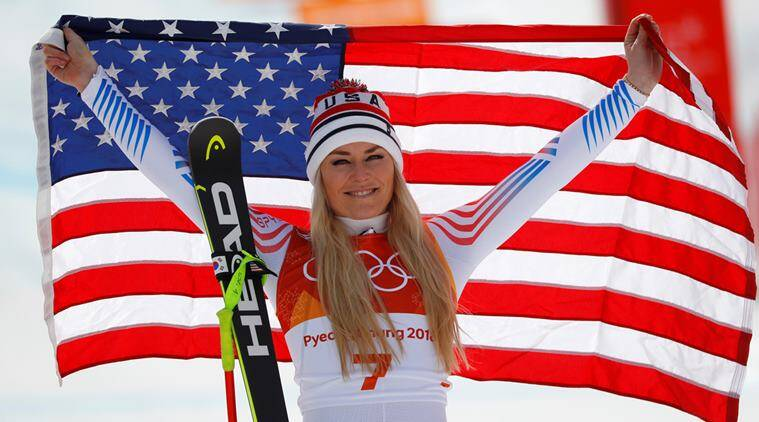 Bronze medallist Lindsey Vonn of the U.S. celebrates with the Italian flag during the flower ceremony.