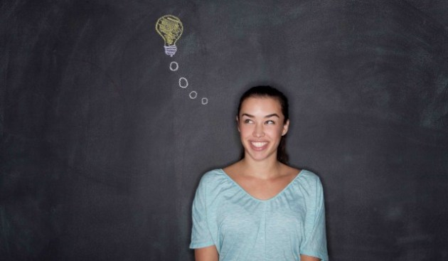 06 Dec 2013 --- Young woman by blackboard with lightbulb --- Image by © David Jakle/Corbis