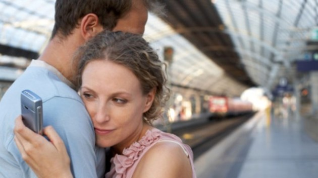 Couple embracing on station platform, woman looking at mobile phone, Separation, Horizontal, Waist Up, Indoors, Side View, Mobile Phone, Caucasian Appearance, Standing, Embracing, Train, Railroad Station, Berlin, Day, Mid Adult, Color Image, Railroad Station Platform, Series, Two People, Mid Adult Men, Mid Adult Women, Distracted, Photography, Mid Adult Couple, Infidelity, Travel, Capital Cities, Wireless Technology, Adults Only, Girlfriend, Boyfriend, msnbc stock photography