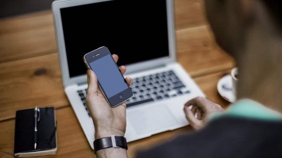 Un ragazzo al computer guarda il suo smartphone