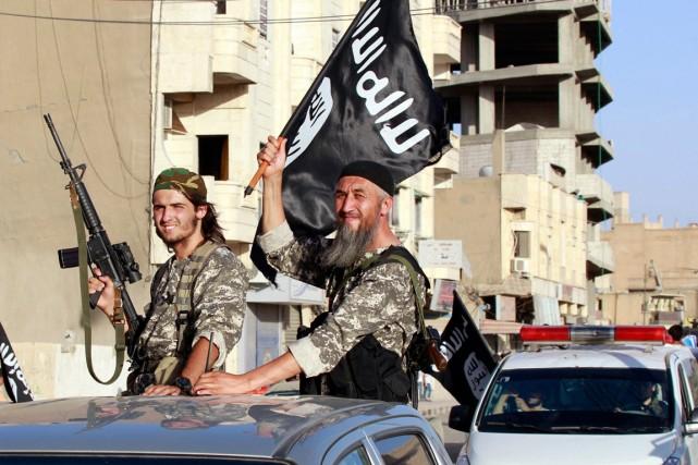 Des combattants de de l'État islamique (EI) paradent... (PHOTO ARCHIVES REUTERS)
