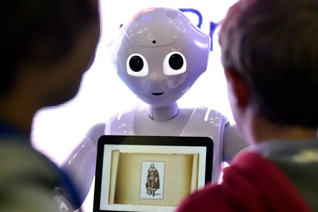 Des enfants interagissent avec un robot humanoïde, lors... (Photo GERARD JULIEN, archives AFP)