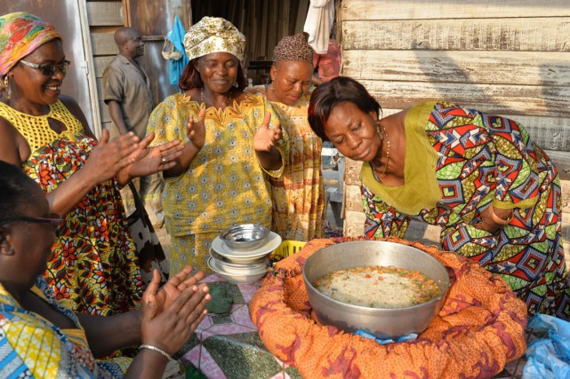 Une femme ouvre le «sac-marmite» dans lequel elle... (PHOTO REINNIER KAZE, AFP)