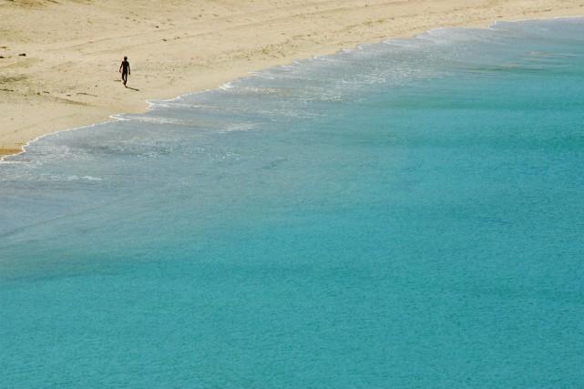 Un touriste marche sur une plage de l'île... (Photo Bazuki Muhammad, archives REUTERS)