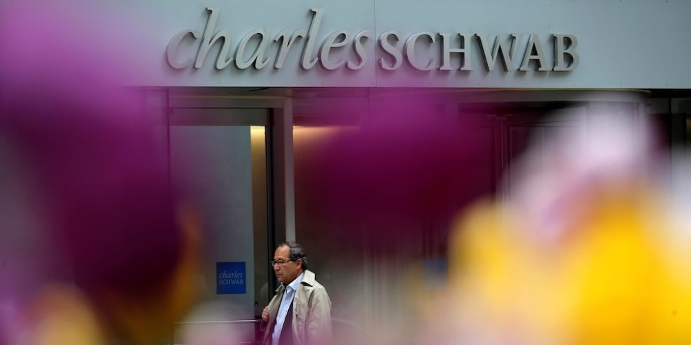 A man walks past a Charles Schwab investment branch in Chicago.
