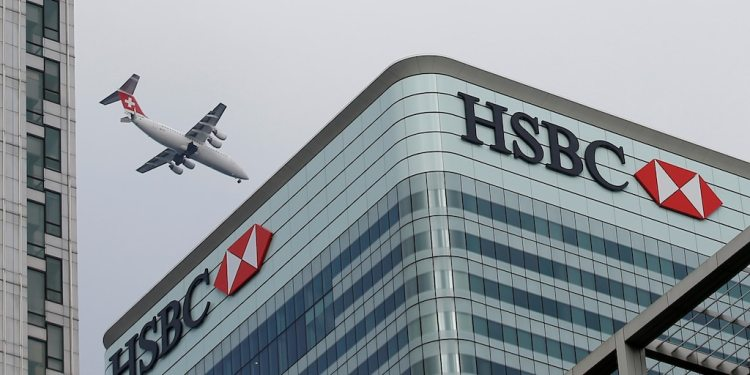 FILE PHOTO: An aircraft flies past the HSBC headquarters building in the Canary Wharf financial district in east London February 15, 2015.   REUTERS/Peter Nicholls/Files