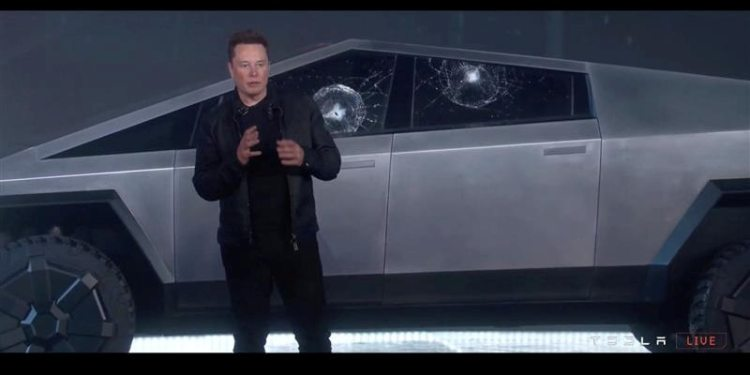 Tesla Chief Executive Elon Musk stands in front of the cracked windows of company's first electric pickup truck, the Cybertruck, after it was unveiled and a metal ball was thrown at the windows, in Los Angeles, California U.S., November 21, 2019, in this frame grab made from the livestream of the unveiling event. Tesla/Handout via REUTERS
