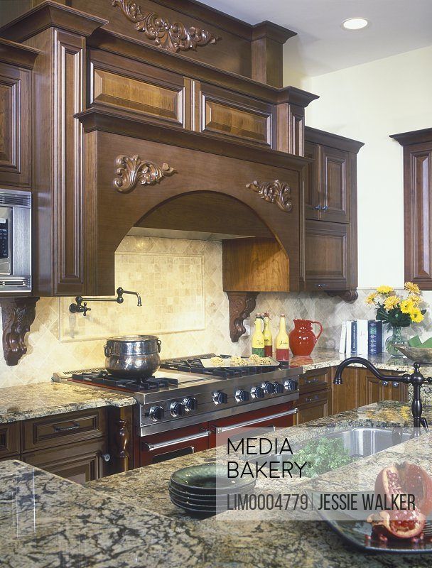https www mediabakery com lim0004779 kitchens detail of cooking area with stove top and work island traditional dark wood ornate exhaust hood cream and brown veined marble hot water faucet over stove html