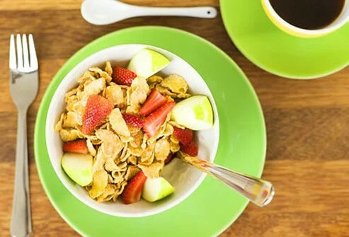 A bowl of cereal with sliced strawberries and apples.