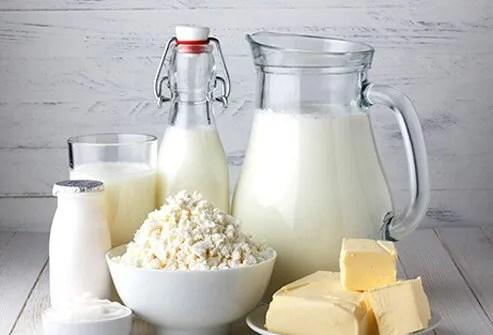 An assortment of different cheeses, milk, butter, and yogurt.