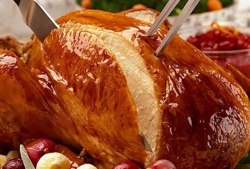 Knife and fork carving roasted turkey.