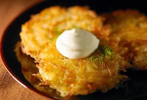 Three potato <i>latkes</i> with  sour cream.