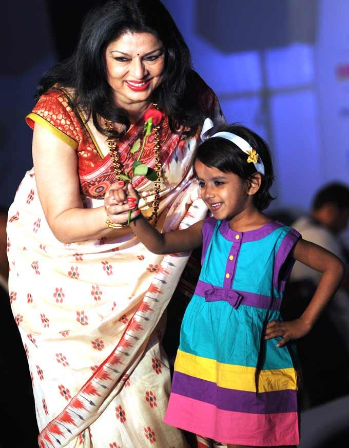 Kiran Helps A Little Girl Walk The Ramp At The Smiles Foundation Fashion Show