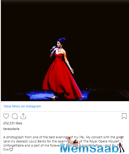 In this photo, we can see the actress performing live on the stage. She looked stunning in a red gown.