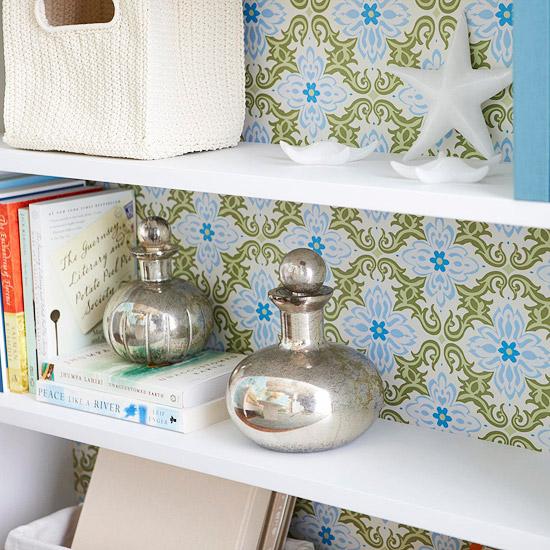 Foto Tapezierte Rückwand in einem Bücherregal davor Dekogegenstände