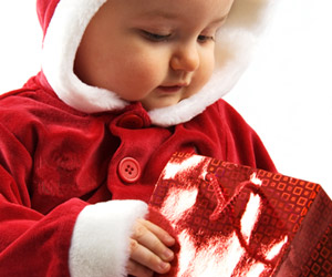baby in santa costume holding present