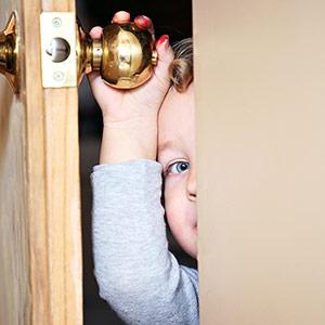 toddler hiding behind door