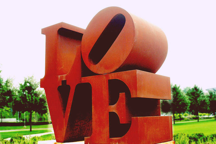 A large public art structure with alphabetical blocks spelling out 'LOVE'.