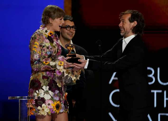 """Taylor Swift, from left, Jack Antonoff and Aaron Dessner accept the award for album of the year for """"Folklore""""at the 63rd annual Grammy Awards at the Los Angeles Convention Center on Sunday, March 14, 2021. (AP Photo/Chris Pizzello)"""