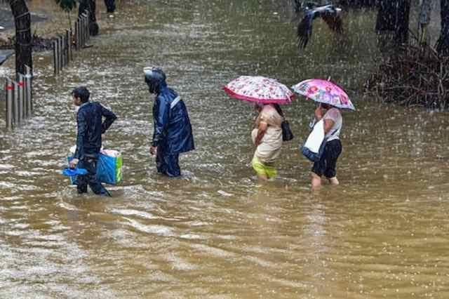 मुंबई के परेल इलाके में भारी बारिश के बाद सड़क पर जलजमाव के बाद वहां से गुजरते लोग. (पीटीआई फाइल फोटो)