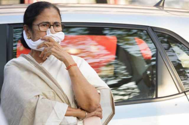 FWest Bengal Chief Minister Mamata Banerjee covers her face with a cloth during the coronavirus pandemic.