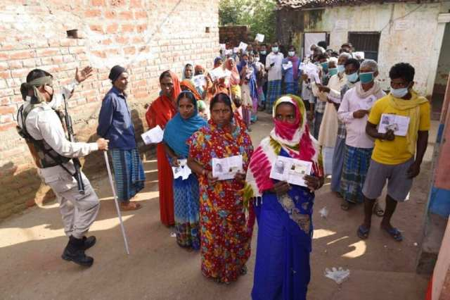 Voters display their identity cards outside a polling station at Paliganj, in Bihar. (AP Photo/Aftab Alam Siddiqui)
