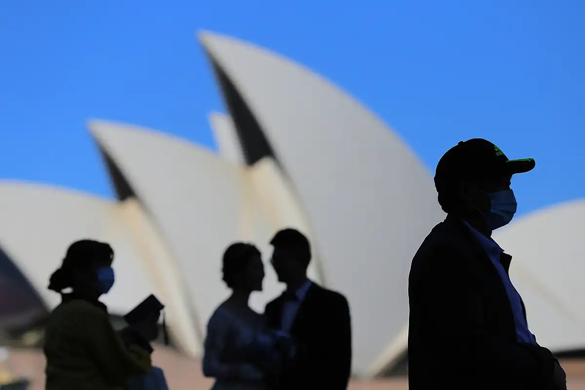 Australia axes overseas travel and large gatherings to slow covid ...