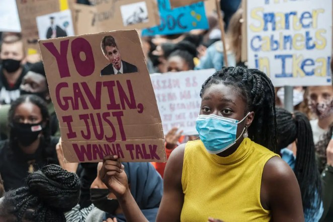 Protestor holds placard reading 'Yo Gavin, I just wanna talk'
