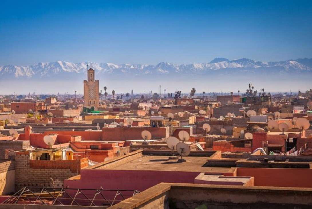 Copper roofs of Marrakesh buildings with mountains in distance