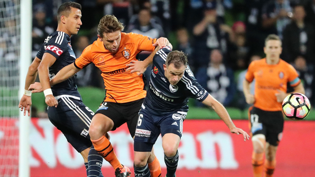 Brisbane Roar's Brett Holman and Victory's Leigh Broxham tussle for the ball at AAMI Park.