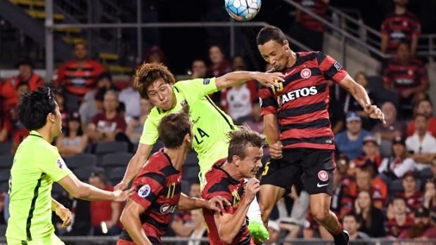 The Wanderers' Kearyn Baccus flies high for a header against Urawa on Tuesday night.