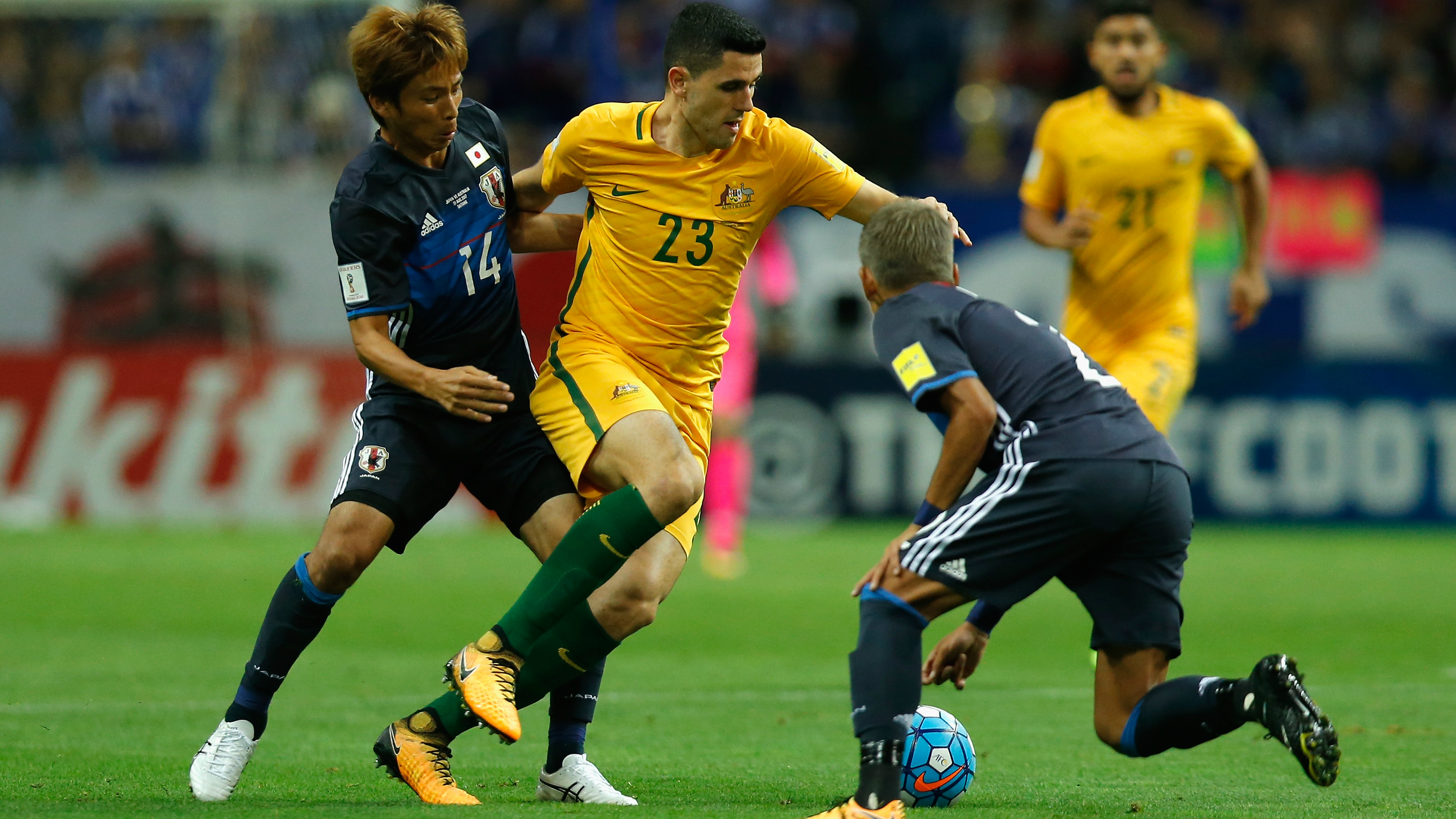 Caltex Socceroos playmaker Tom Rogic looks to take on a couple of Japanese defenders.
