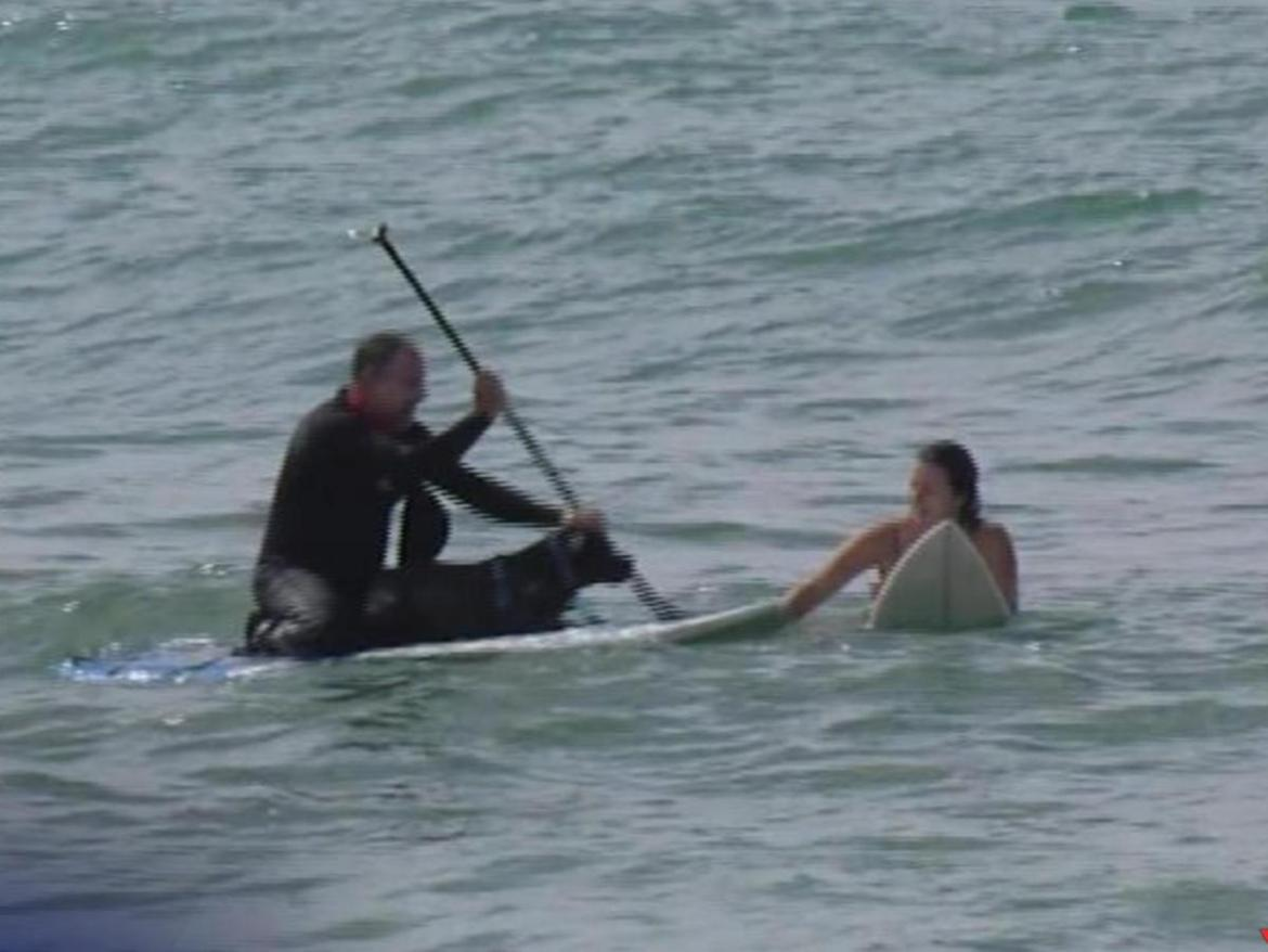 Surfers went out to rescue a woman who was swept out to sea trying to rescue her dog.