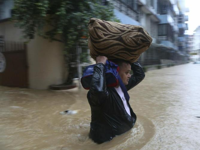 A Nepalese man wades with his belonging through a flooded street in Kathmandu, Nepal, Friday 12 July 2019. Heavy rains from Thursday night caused chaos throughout the country. According to the meteorological department, precipitation throughout the country will probably continue until Sunday. (Photo AP / Niranjan Shrestha)