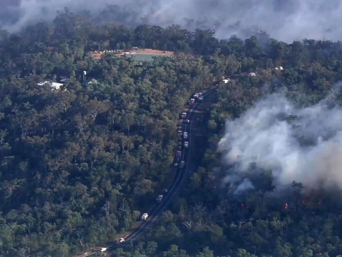 A convoy of firetrucks move along the road near the Wooroloo fire.