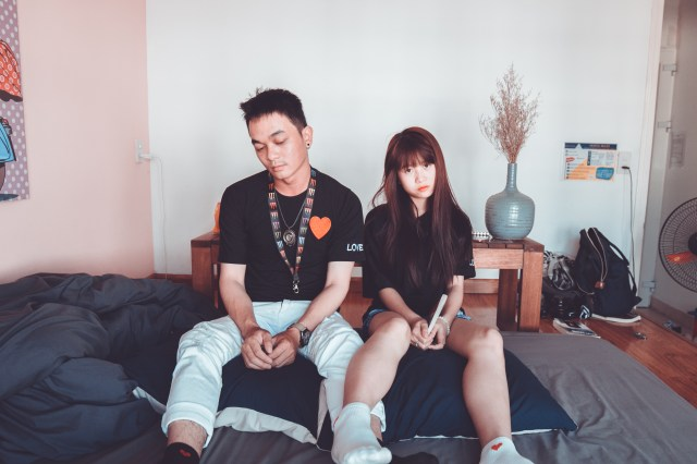 Man and Woman Wearing Black Shirts Sitting on Bed
