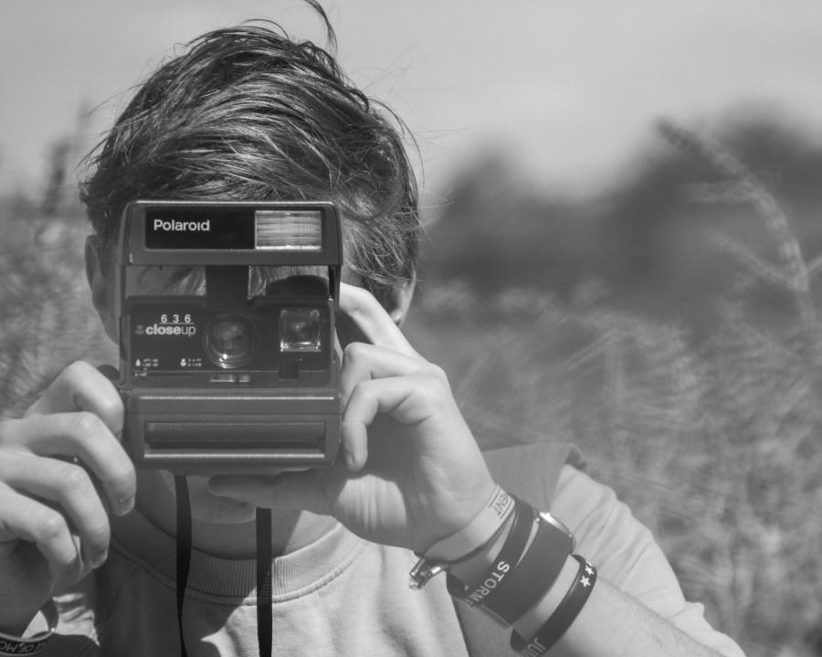 Photo of Person Holding Polaroid Camera
