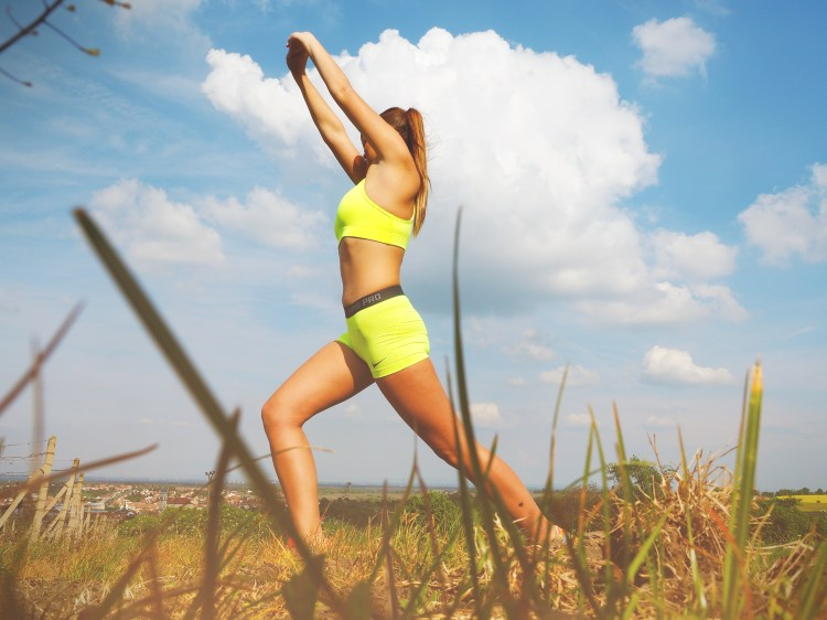 Woman in Yellow Sports Bra Stretching Near Green Grass Field