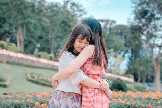 Candid Photography of Two Female Hugging
