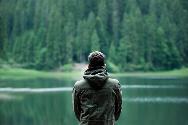 Photo of Man Wearing Hooded Jacket in Front of Body of Water