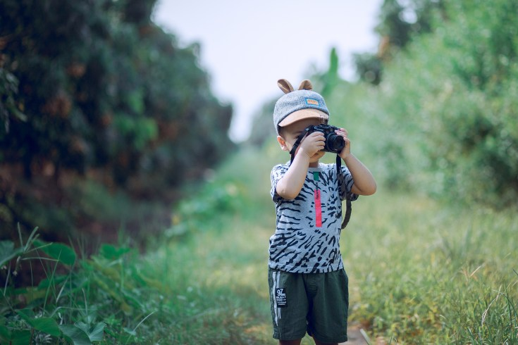 little boy is holding a camera while taking pictures at the farm