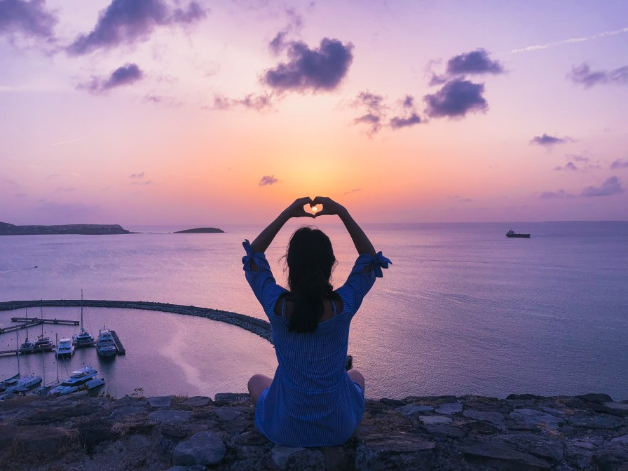 Woman Sitting on Rock Doing Heart Hand Gesture