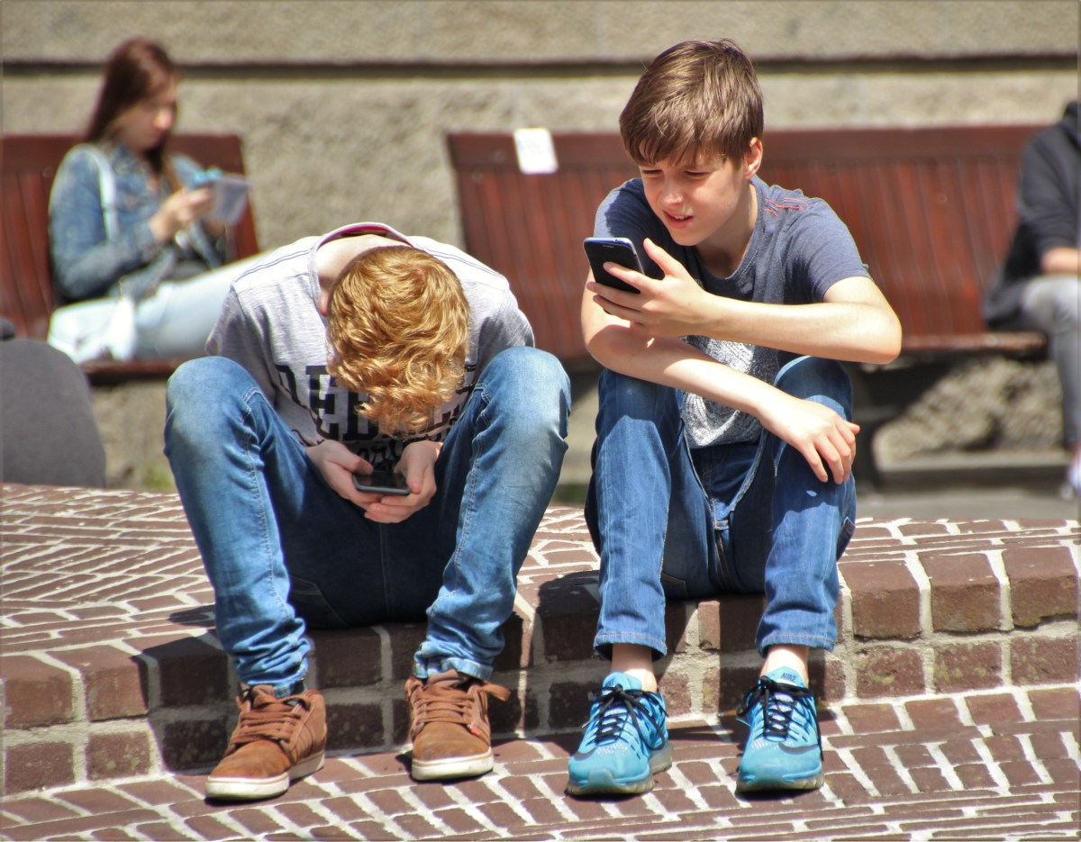 2 Boy Sitting on Brown Floor While Using Their Smartphone Near Woman Siiting on Bench Using Smartphone during Daytime