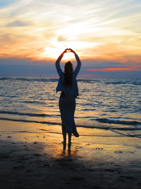 Happy Lonely Girl Wallpaper Woman With Arms Up Making Heart Sign While Standing On