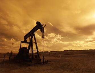 An in-ground oil pumping unit sits against a golden cloudy sky.