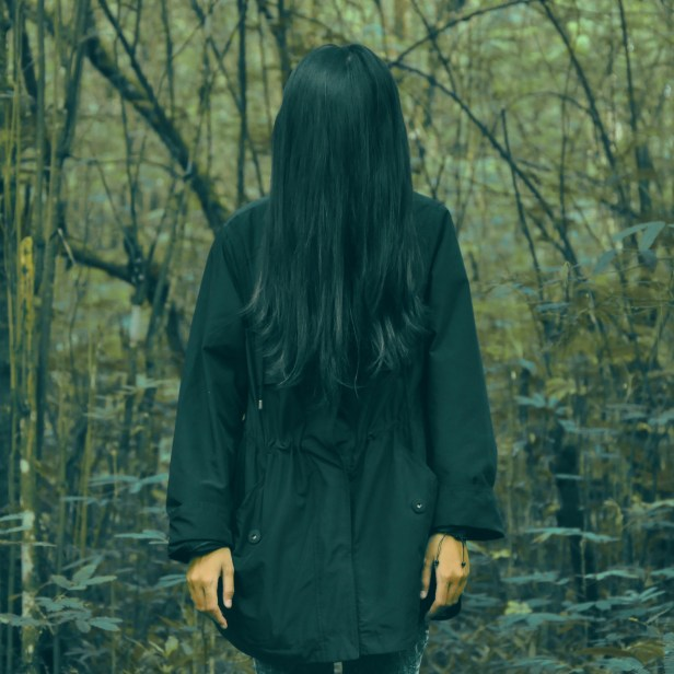 Person in Black Coat Standing in Forest